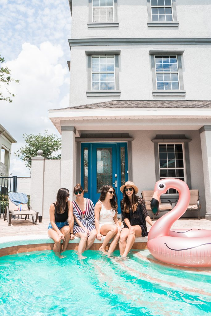 4 girls sitting poolside at vacation rental in Florida // where to stay near Disney World with a big group