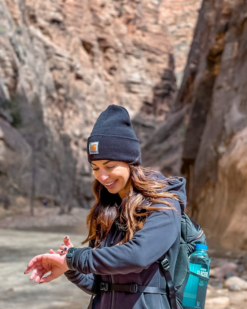 girl hiking in Zion checking watch / Paceline - the app that pays you to workout